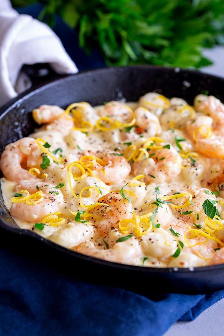 cast iron skillet of shrimp gnocchi garnished with lemon zest on a blue napkin