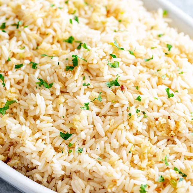 overhead view of rice with garlic and herbs on top
