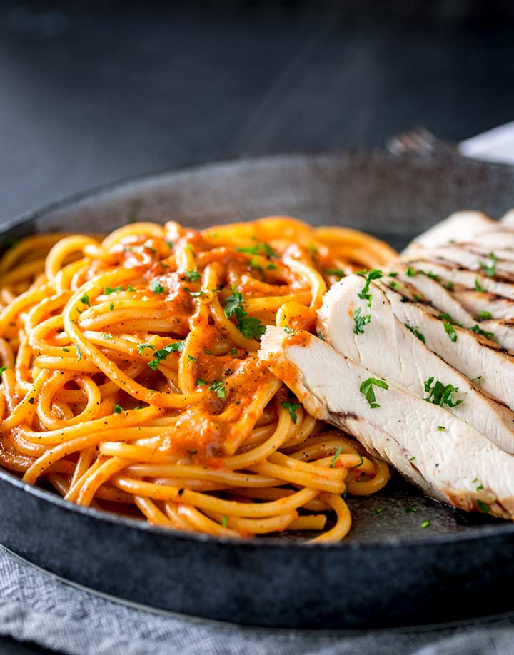a black plate with hot pasta and sliced chicken