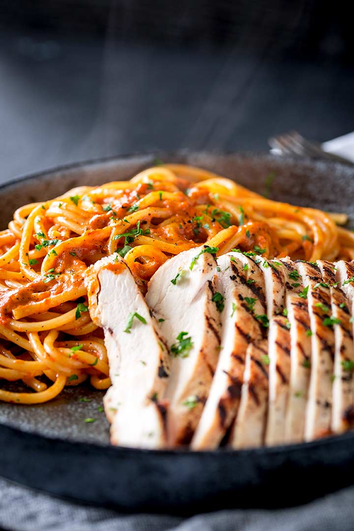 steam rising from a pile of red pepper pasta with some chicken next to it
