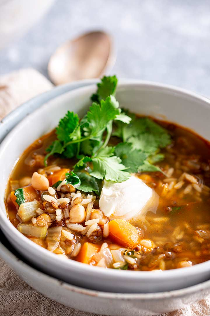 a bowl of moroccan soup garnished with sour cream and cilantro