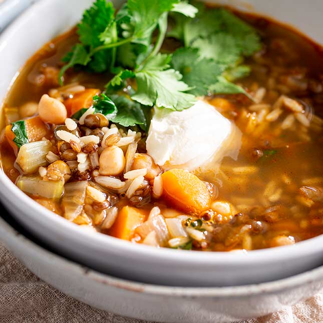 close up on a lentil soup with sour cream and cilantro garnish
