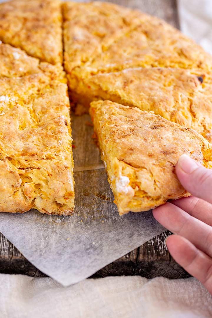 a hand picking up a triangular slice of pumpkin bread
