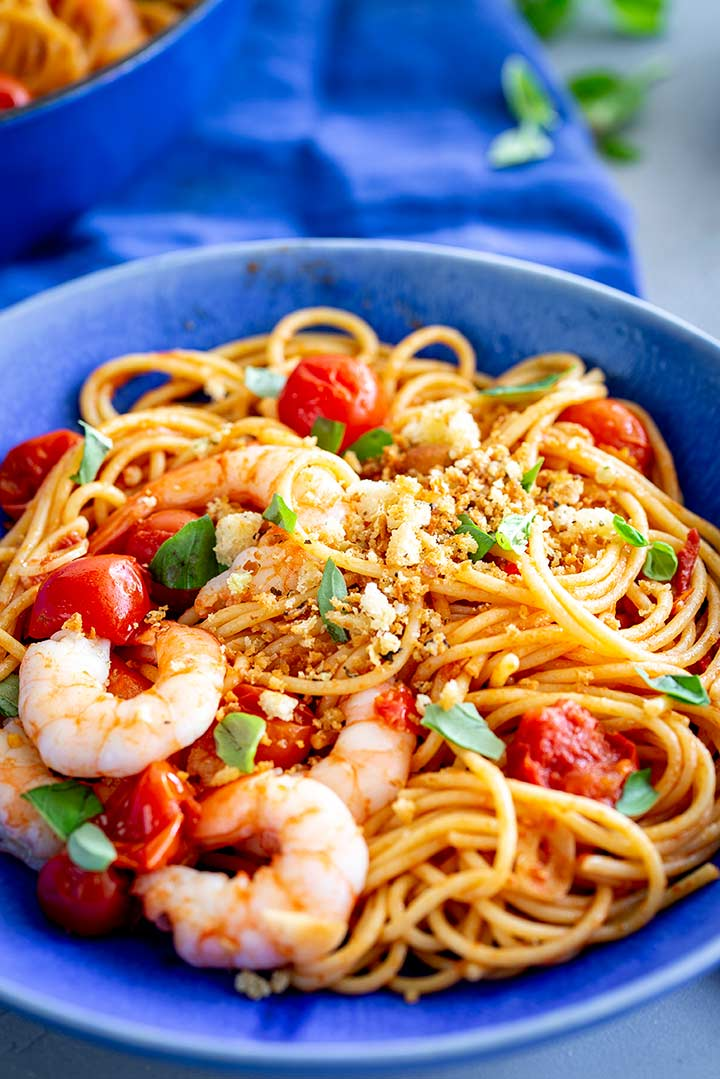 a blue plate on a blue napkin filled with spicy shrimp pasta
