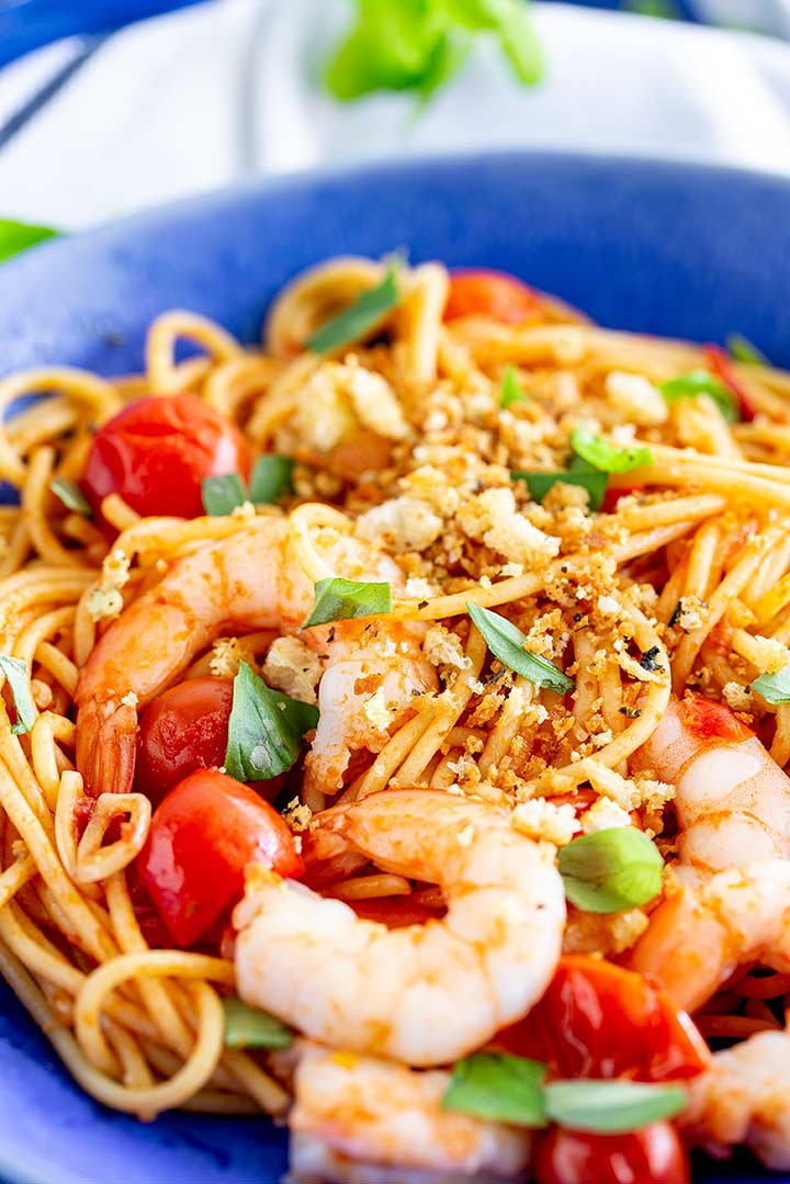 tomato spaghetti with shrimp on a bright blue plate