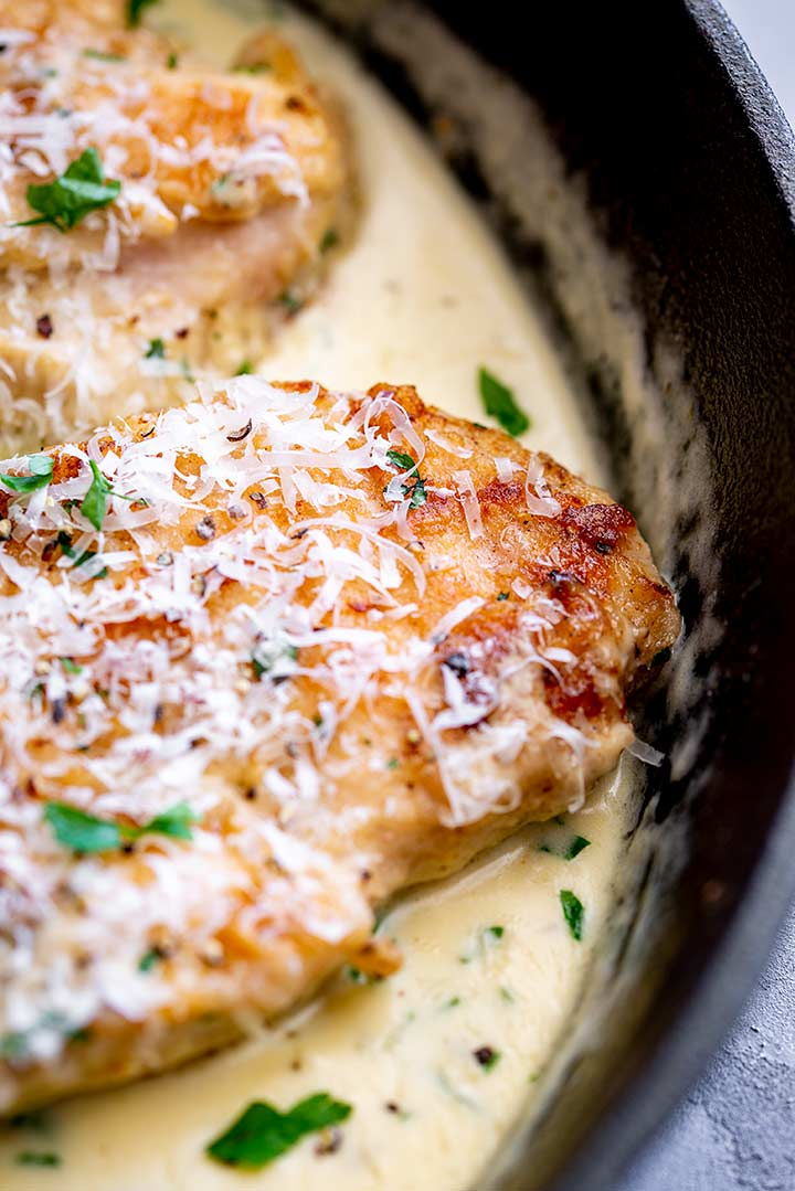 close up on a golden chicken breast topped with parmesan