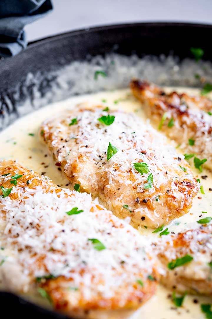 close up on a chicken breast covered in parmesan with fresh herbs