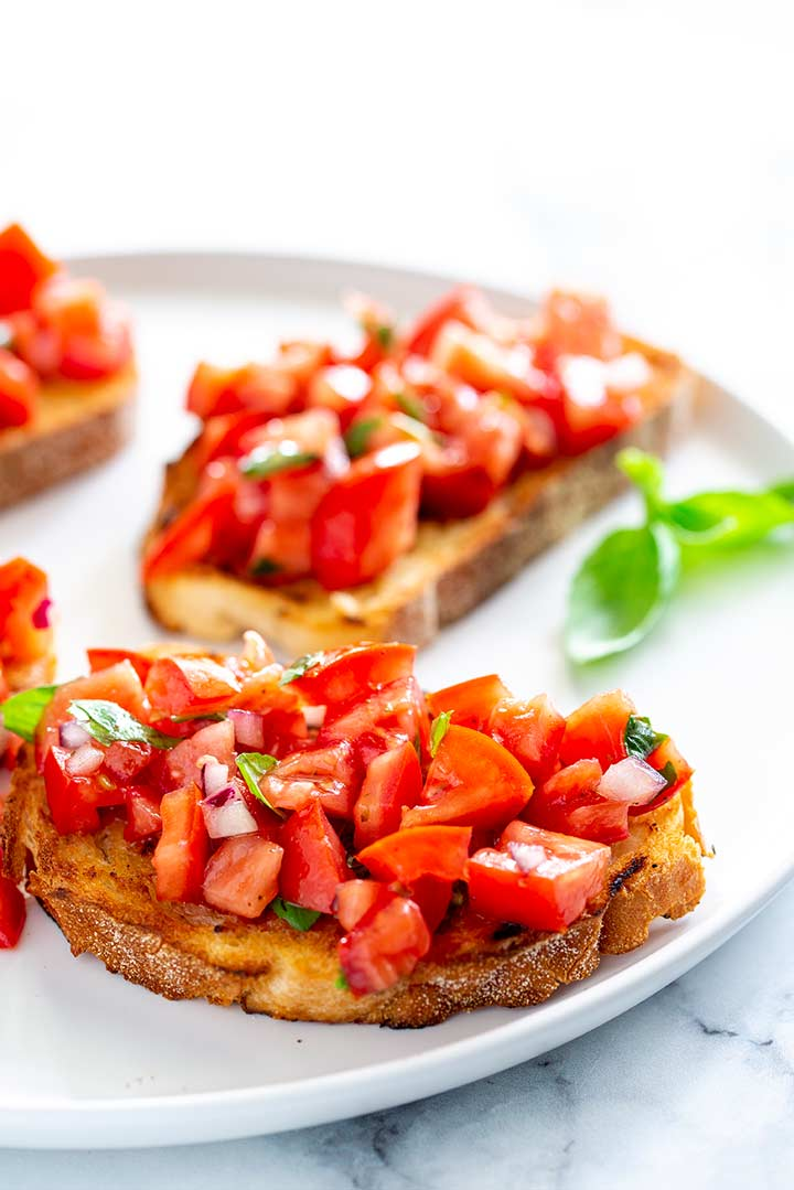 chopped tomato and onion on top of a bruschetta on a white plate