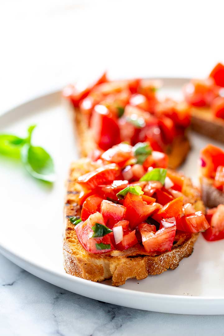 a backlit photo of bruschetta on a white plate