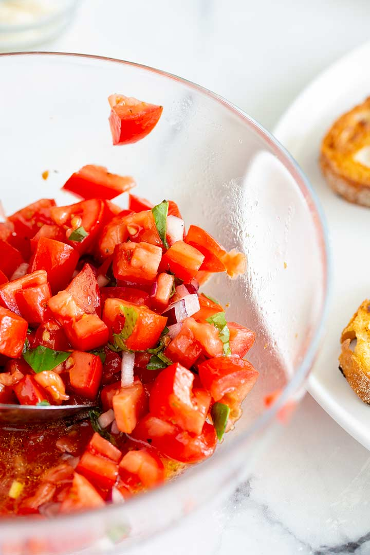 chopped tomato, basil and onion in a glass bowl