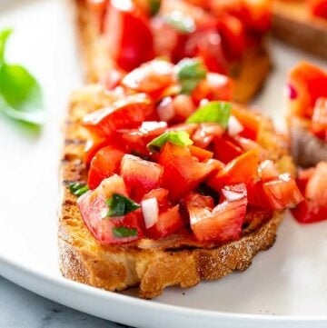 close up on the chopped tomatoes on top of crust bruschetta