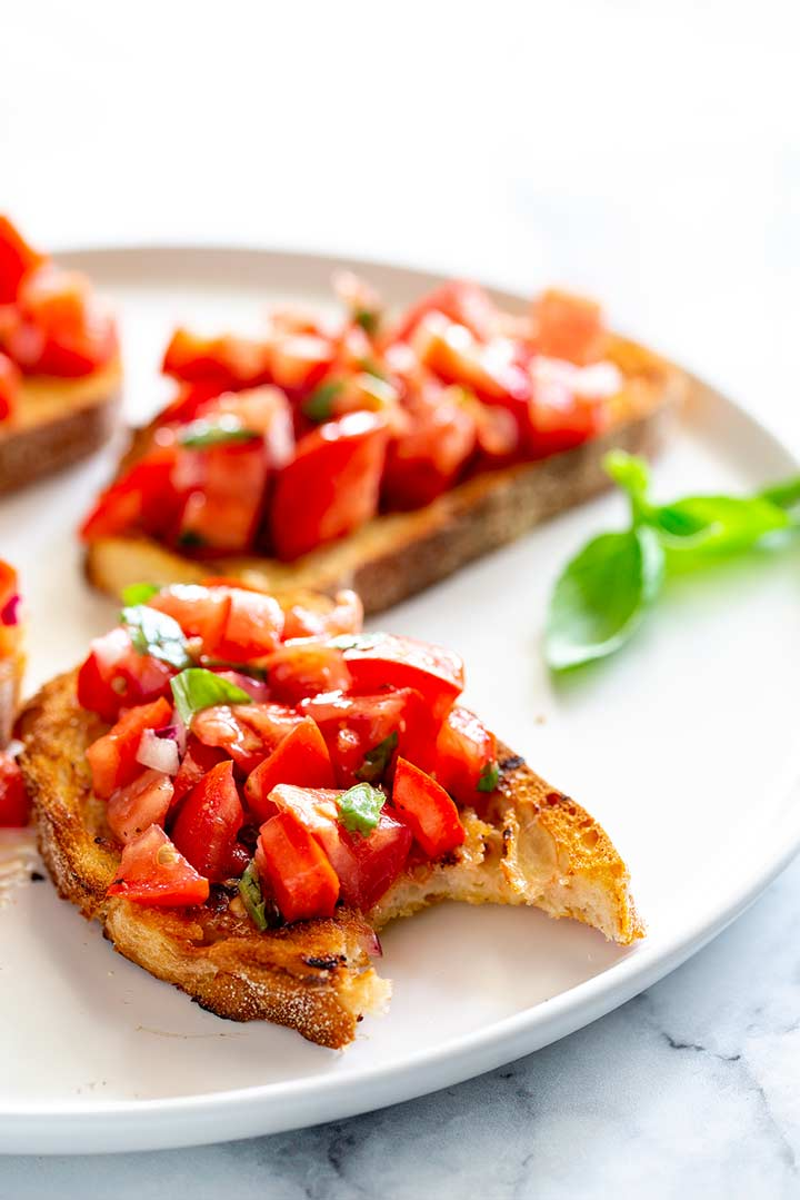 a slice of tomato bruschetta with a bite taken out, on a white plate