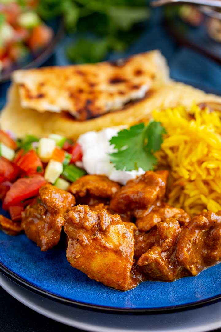 a red curry, rice, naan and salad on a blue plate