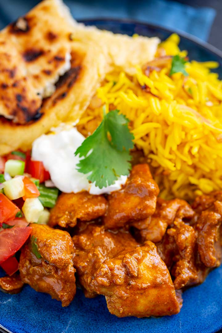 chunks of chicken in a Rogan Josh sauce on a blue plate with pilau rice