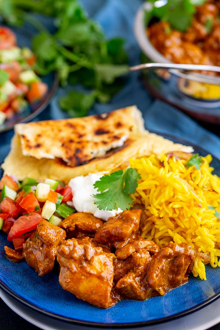 a blue plate of curry with yellow rice, tomato salad and naan bread