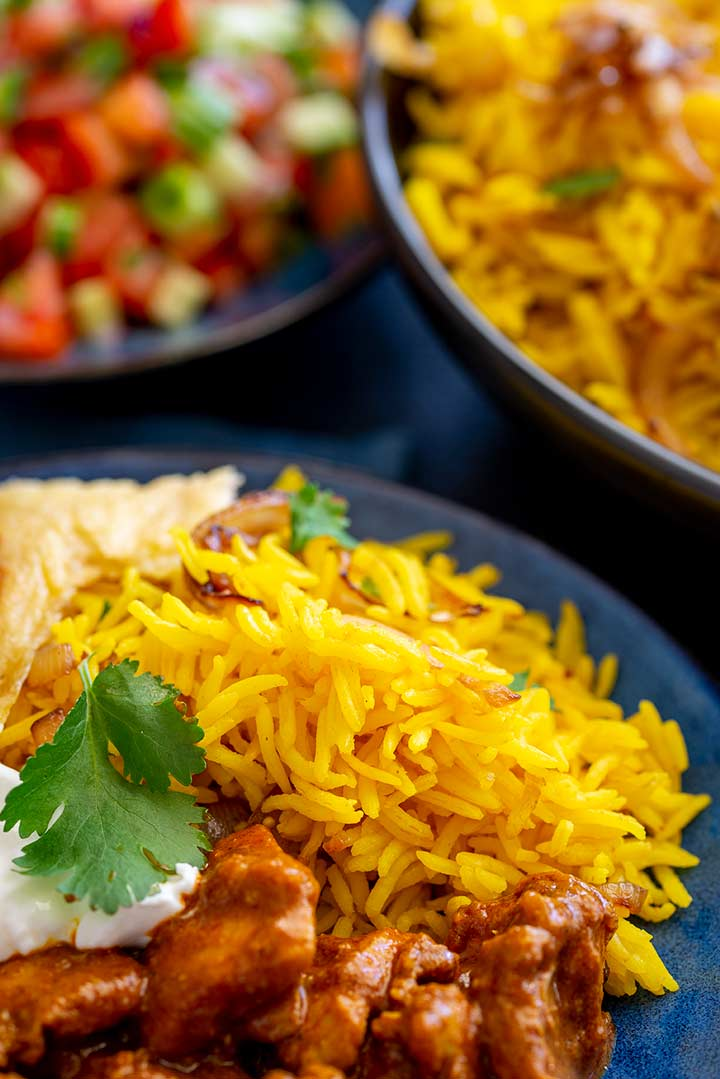 close up on a pile of yellow rice on a blue plate with curry