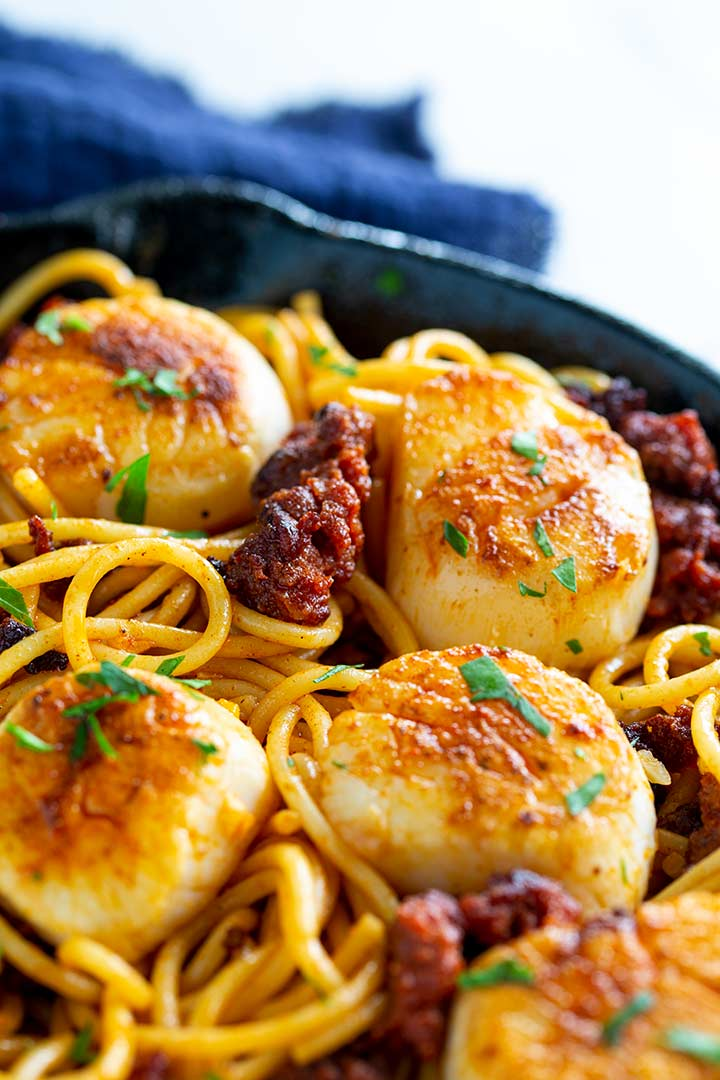 scallop chorizo pasta in a frying pan with a blue napkin behind