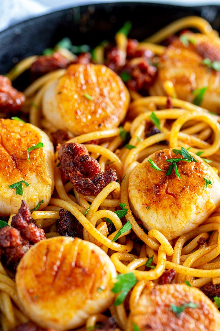 Close up on a seared scallop and a crispy piece of chorizo on a bed of spaghetti