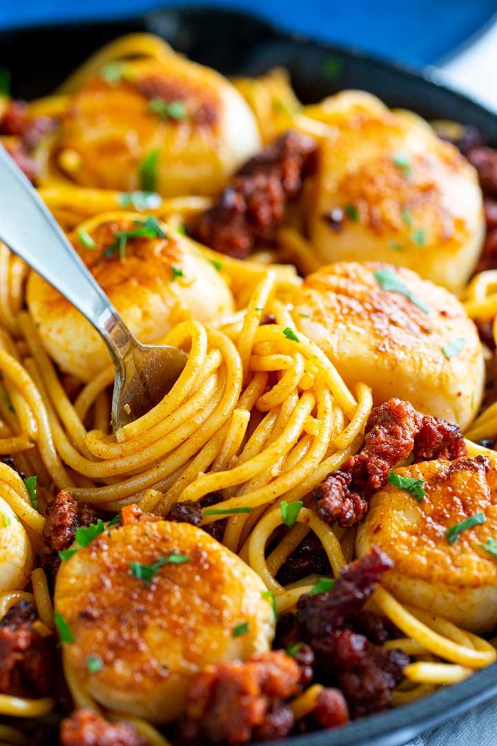 a fork swirling spaghetti with crumbed chorizo and seared scallops