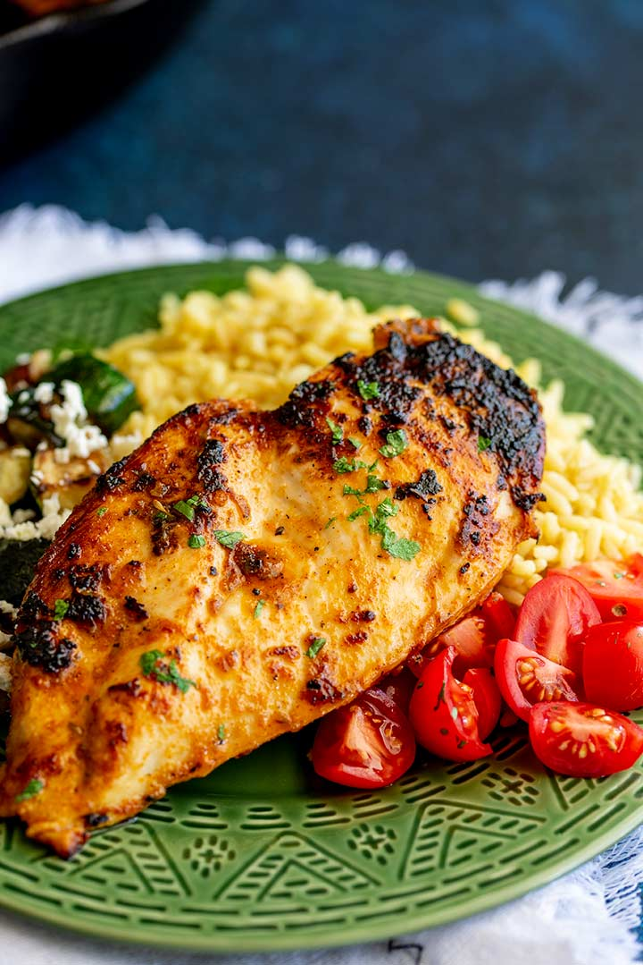 a chicken breast on a bed of yellow rice with tomatoes on the side