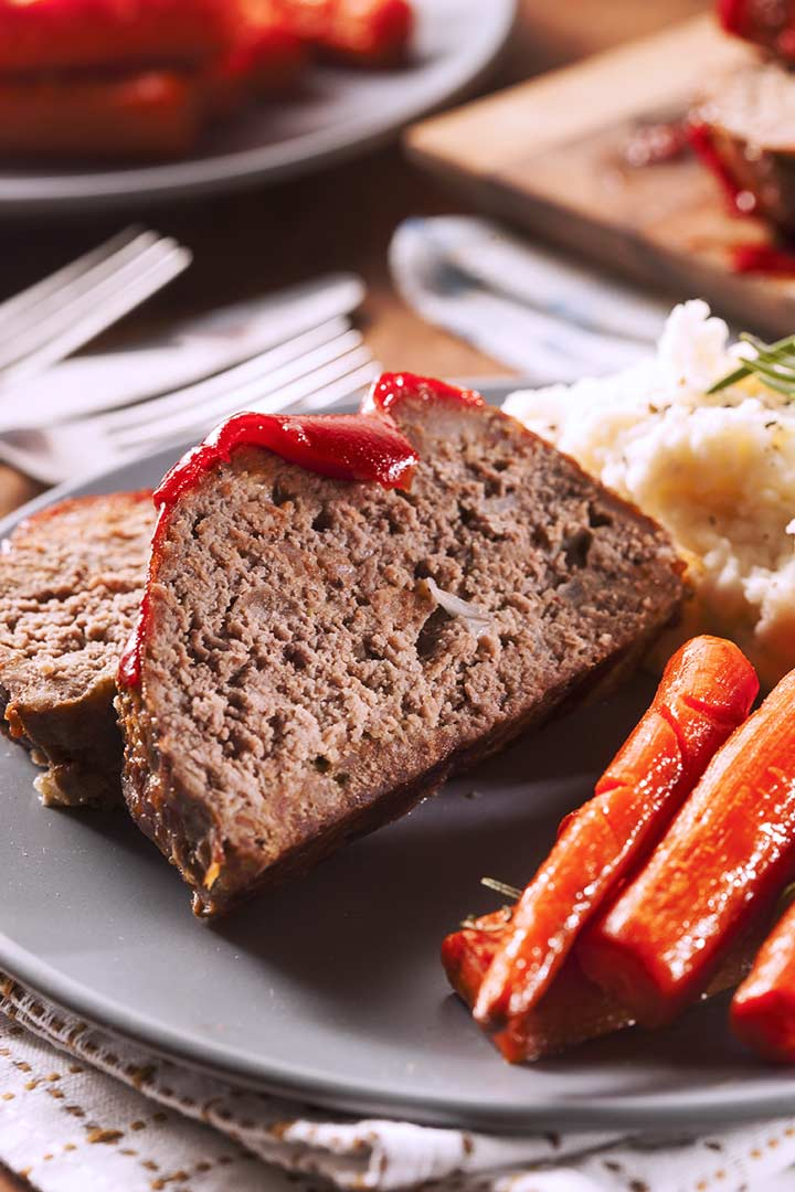 2 slices of meatloaf on a plate with carrots and potatoes