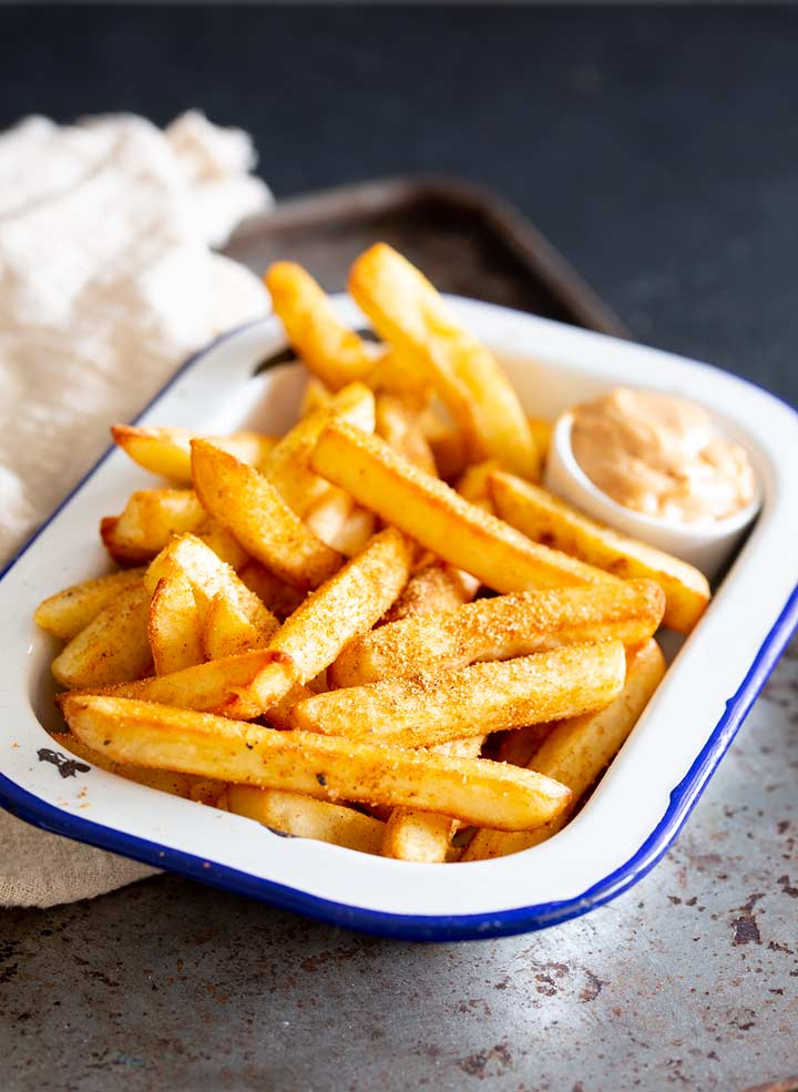 a blue and white metal bowl filled with fries and sauce