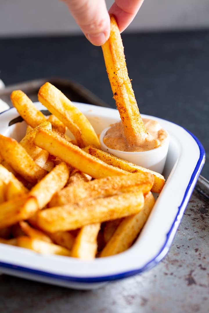 a hot chip being dipped into peri peri mayo