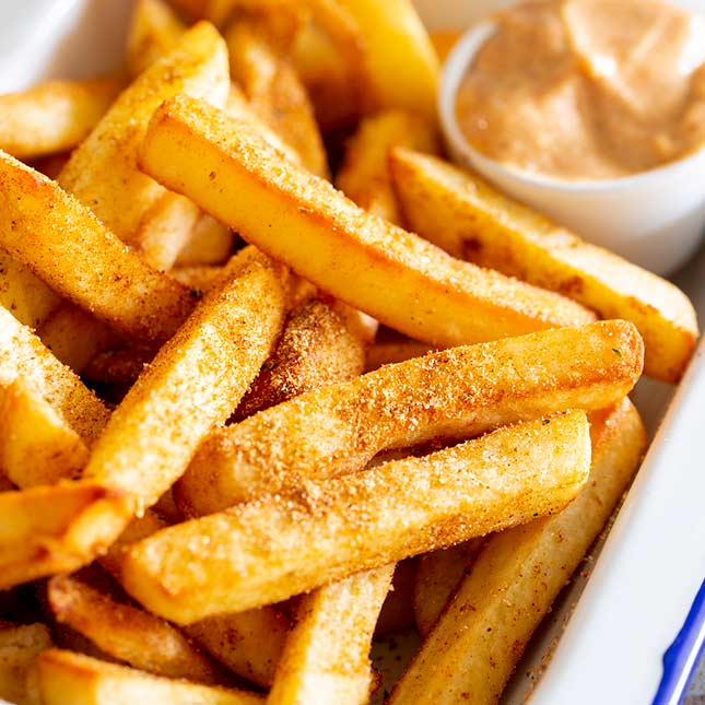 a close up on peri peri fries showing the seasoning on them