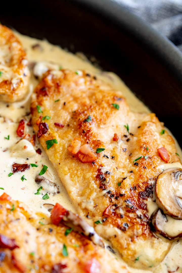a chicken breast in a black skillet of creamy sauce with sliced mushrooms and bits of bacon