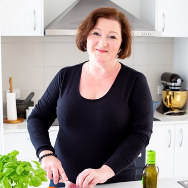 a lady stood in a white kitchen chopping a tomato