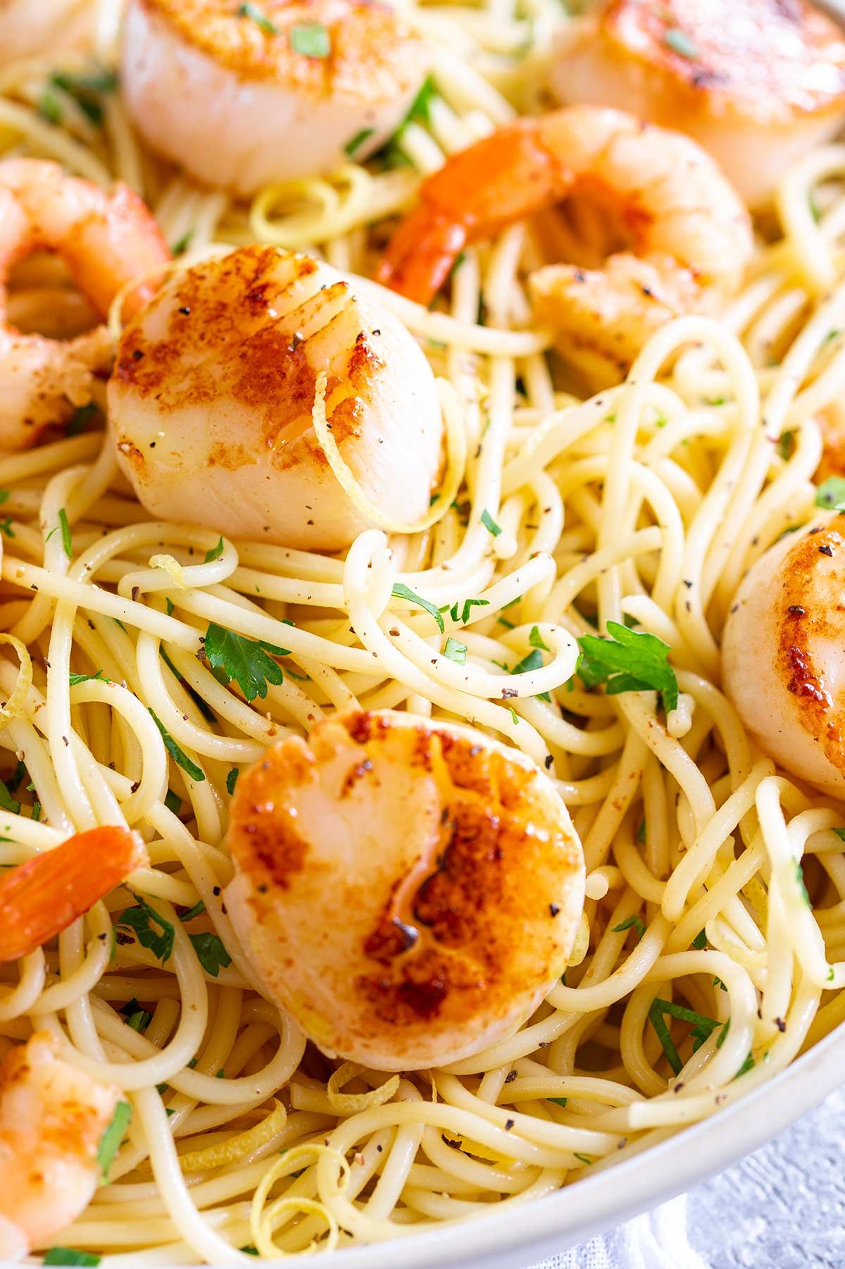 a seared scallop on a bed of garlic pasta