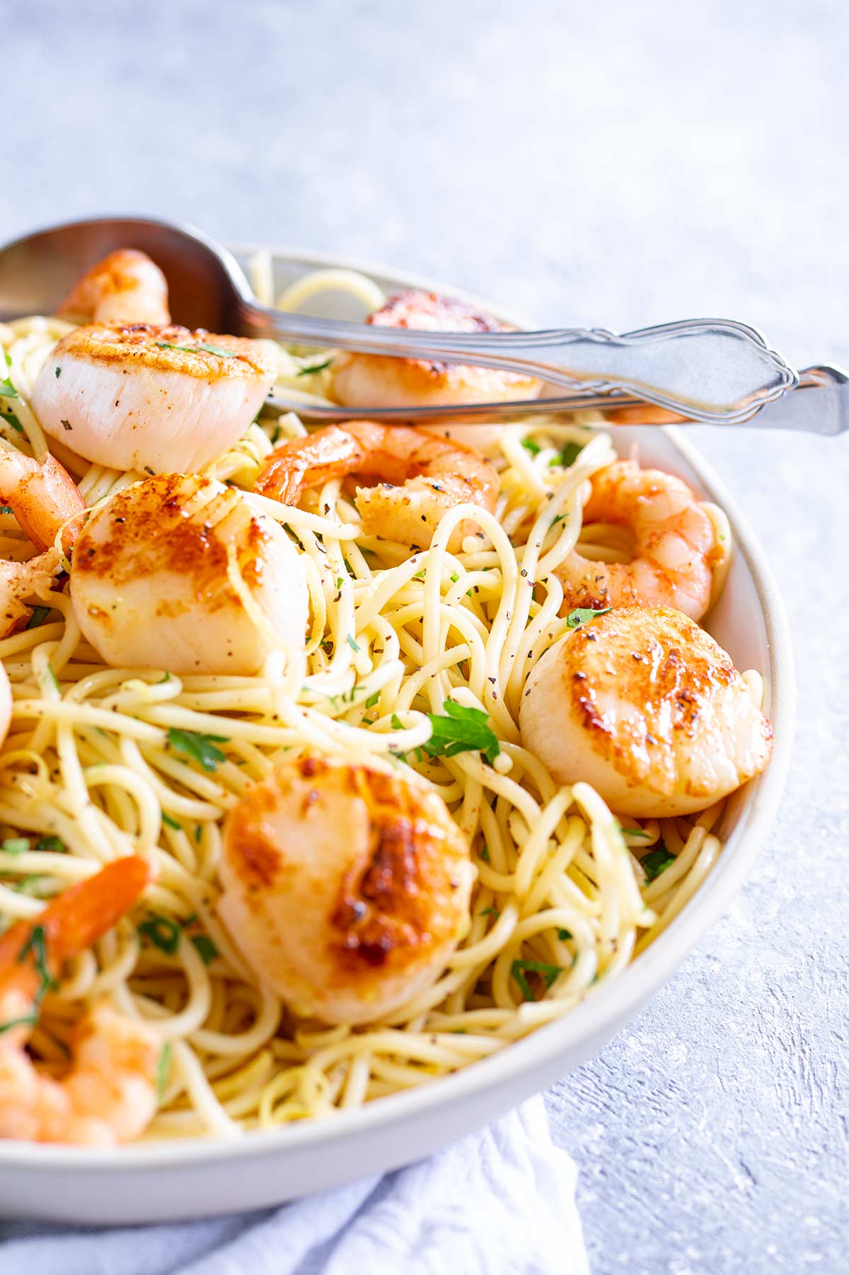 a silver spoon in a bowl of seafood pasta